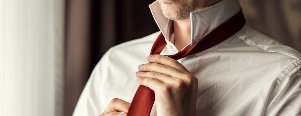closeup of man with white button up dress shirt, collar flipped up, tying a red necktie