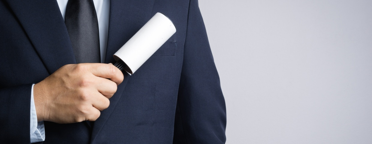 closeup of man using lint roller on suit coat, cleaning and care concept