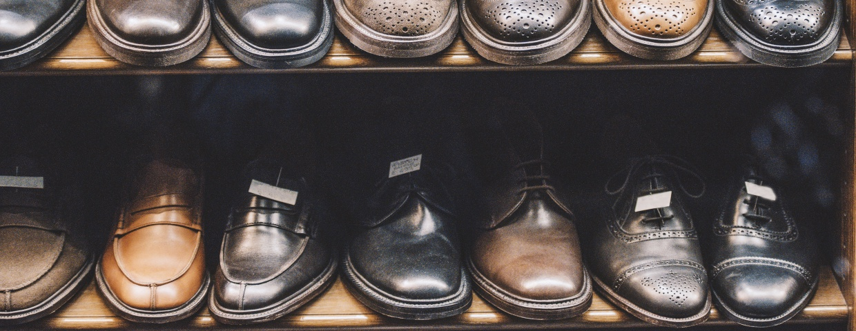 closeup of mens dress shoes on shelf, varying styles and colors