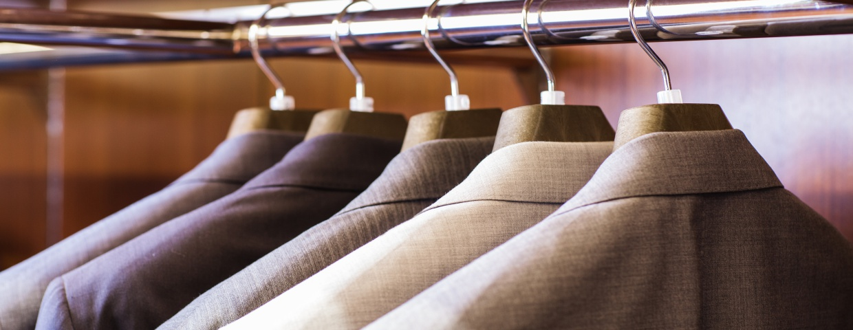 closeup of mens suits hanging up, multicolored suits