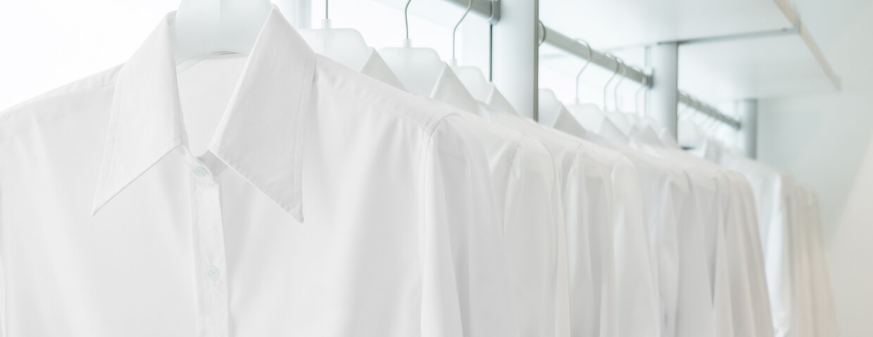 multiple white button up shirts hanging on white built-in cloths racks