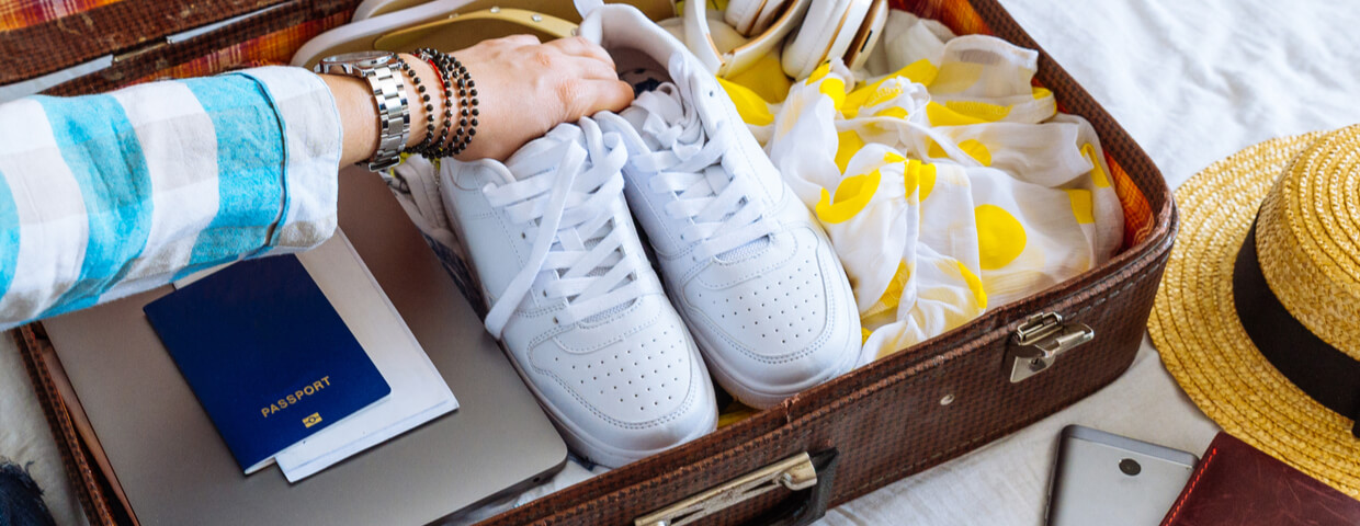 closeup of woman's suitcase open, packing concept, woman putting white sneakers into suitcase