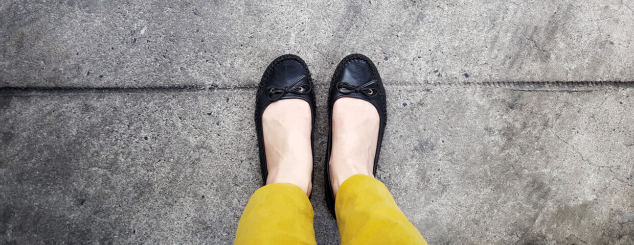 top view, selfie of woman's feet wearing mustard-yellow trouser and black shoe standing on a concrete floor