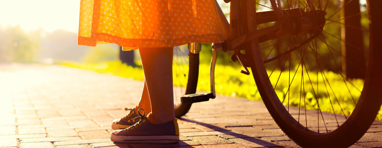 Girls legs and long vintage orange skirt next to bike in the sun
