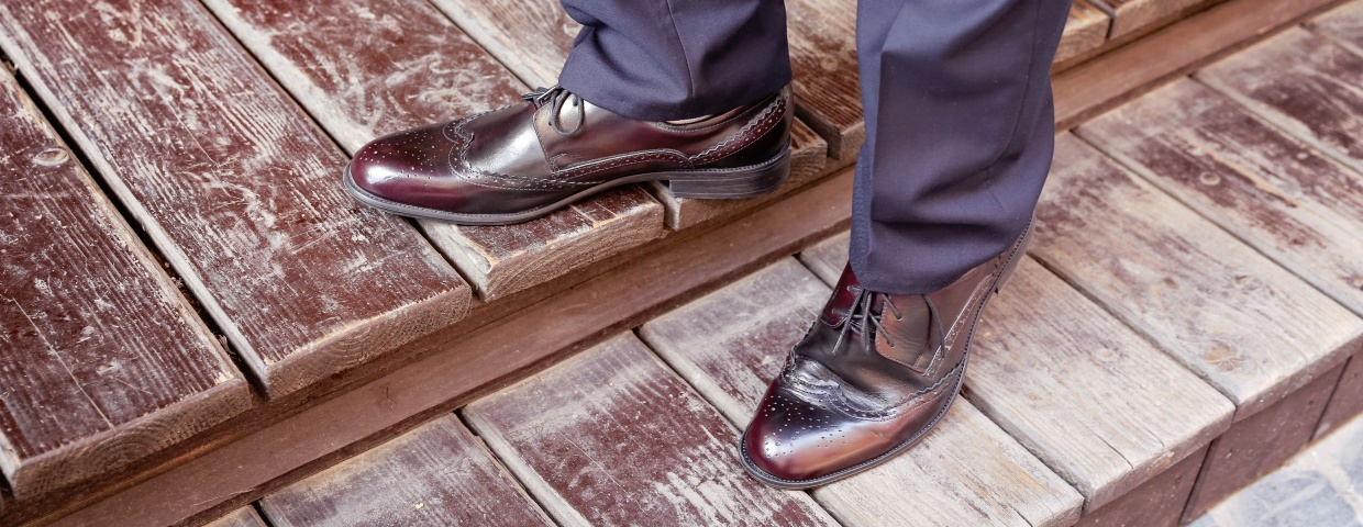 dress shoes concept, closeup of burgundy cap toe dress shoe and navy suit, man standing on wooden stairs