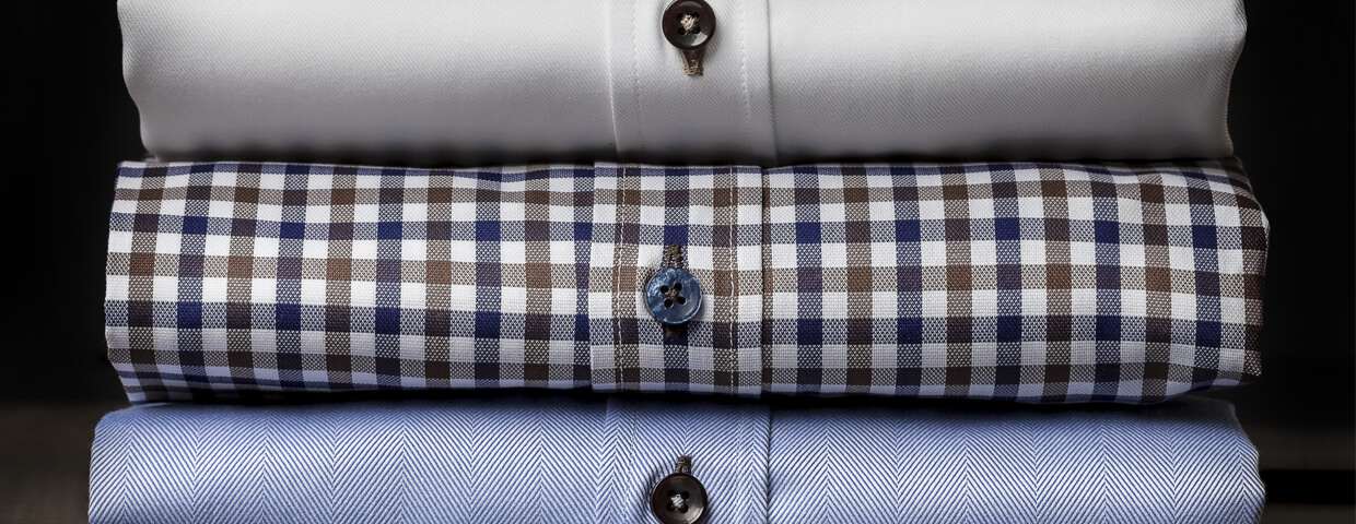 closeup stack of folded mens dress shirts, solid white, plaid, solid blue