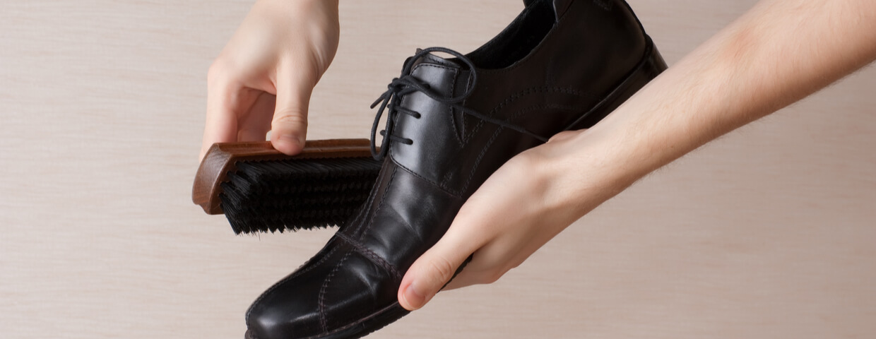 man cleaning and polishing dress shoe