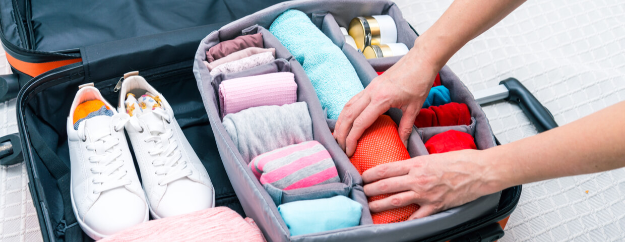 closeup of woman packing clothes into open suitcase