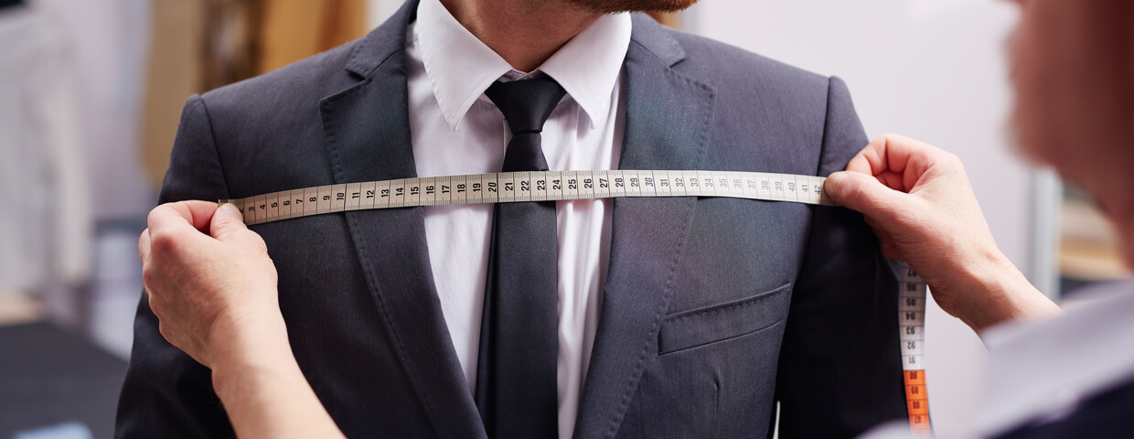 Mid section portrait of tailor fitting suit, measuring width of man who is wearing suit