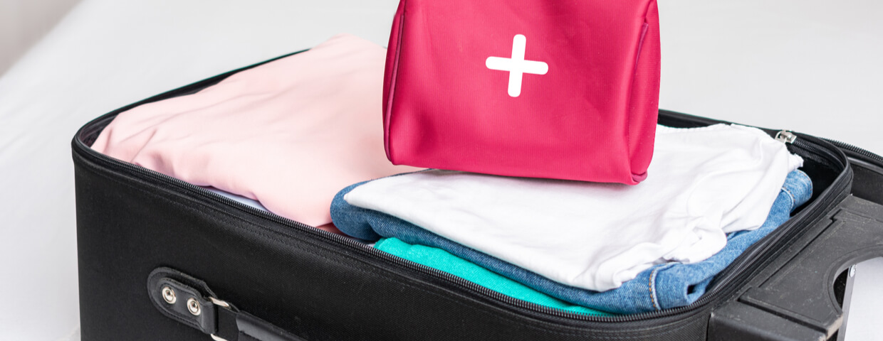 Open suitcase packed with clothes and a first aid kit set on top